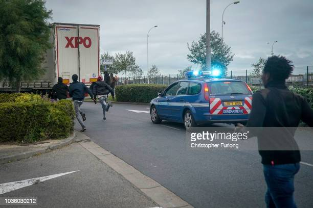 Migrants try to board a truck at Ouistreham ferry port in the hope of reaching the UK on September 12 2018 in Ouistreham France After the clamp down...