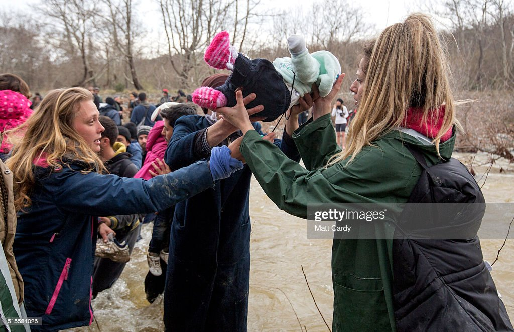 Migrants try to cross a river after leaving the Idomeni refugee camp on March 13, 2016 in Idomeni, Greece. The decision by Macedonia to close its border to migrants on Wednesday has left thousands of people stranded at the Greek transit camp. The closure, following the lead taken by neighbouring countries, has effectively sealed the so-called western Balkan route, the main migration route that has been used by hundreds of thousands of migrants to reach countries in western Europe such as Germany. Humanitarian workers have described the conditions at the camp as desperate, which has been made much worse by recent bouts of heavy rain.