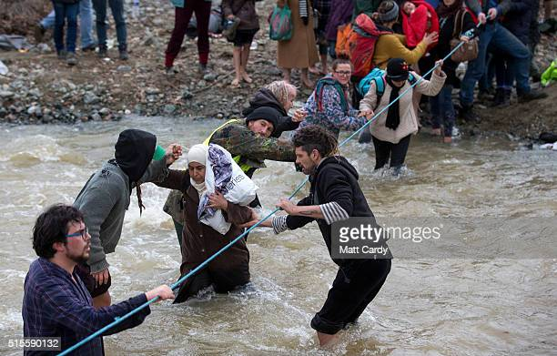 Migrants try to cross a river after leaving the Idomeni refugee camp on March 14 2016 in Idomeni Greece The decision by Macedonia to close its border...