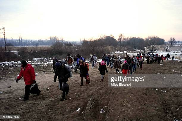 Migrants try to keep warm as they cross the MacedonianSerbian border in early morning sub zero temperatures on January 24 2016 in Miratovac Serbia...