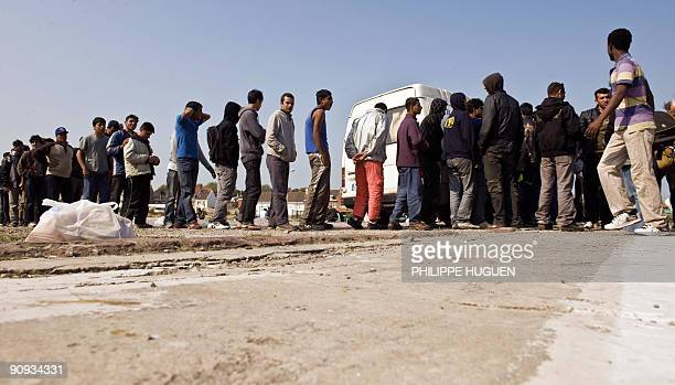 """Migrants trying to get to Britain, mostly from Afghanistan, who leave in a wooded area known as """"the jungle""""in Calais, northern france, queue up..."""