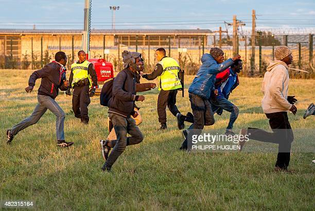 Migrants trying to reach the Channel Tunnel run past policemen in Coquelles near Calais northern France on late July 29 2015 One man died Wednesday...