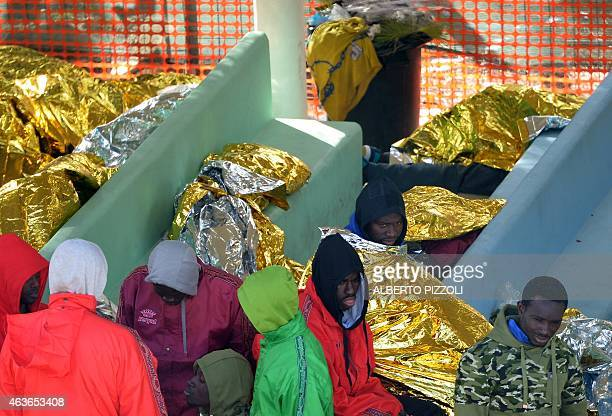 Migrants wait at the Temporary Permanence Centre a refugee camp on February 17 2015 in Lampedusa The Italian coastguard launched a massive operation...
