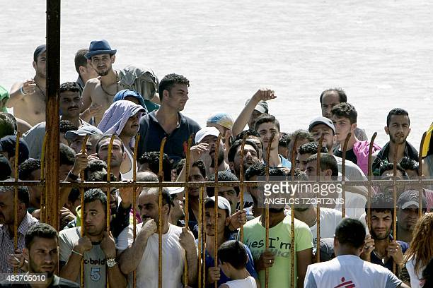 Migrants wait behind a fence outside a stadium in order to be registered by the police on the Greek island of Kos on August 12 2015 The number of...