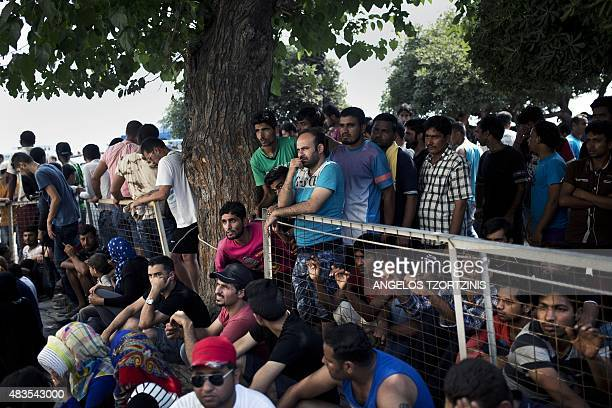 Migrants wait behind a fence to be registered by the police outside a police station on the island of Kos on August 10 2015 The number of migrants...