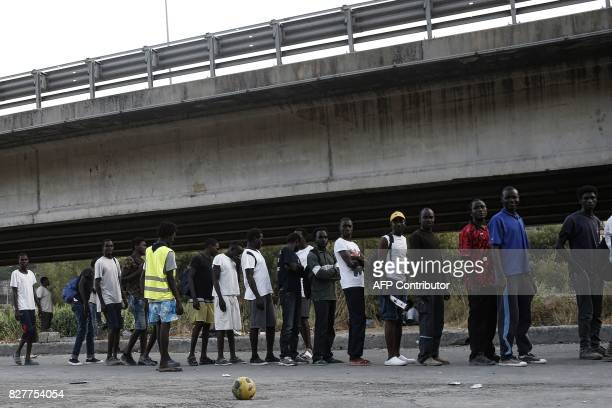 Migrants wait food near the Roya River on August 8 2017 in Ventimiglia close to the French border / AFP PHOTO / Marco BERTORELLO