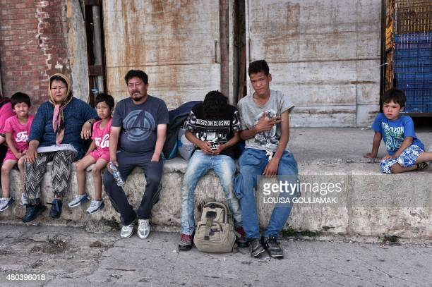 FROISSART*** Migrants wait for a bus after disembarking from a ferry originating from the island on Lesbos at the port of Piraeus near Athens on July...