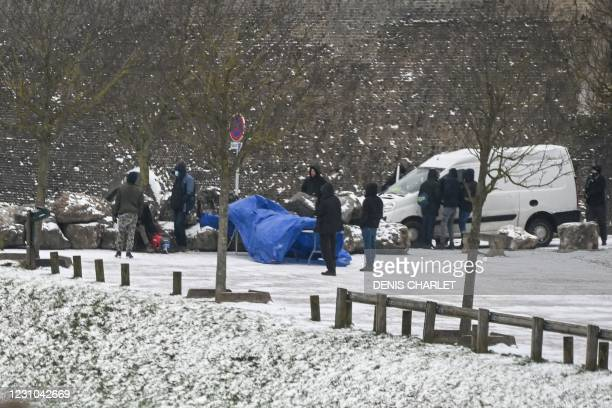 Migrants wait for a food distribution in the northern France port of Calais on February 8, 2021 as the local prefecture announced some 170 additional...