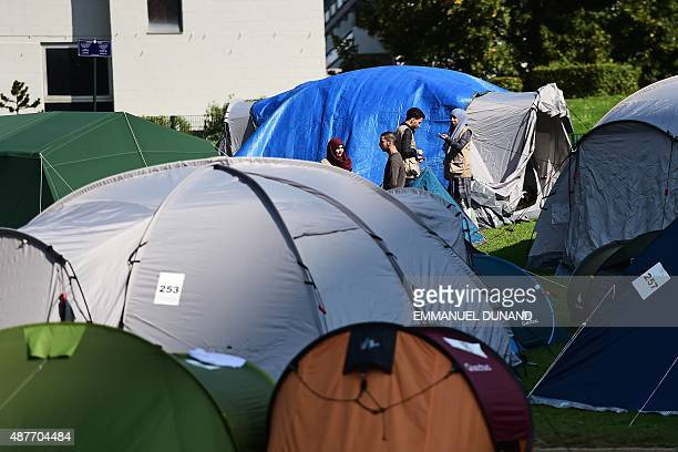 Migrants wait in a makeshift tent camp in a park in Brussels on September 9 as they wait to have their asylum claims processed The camp is situated...