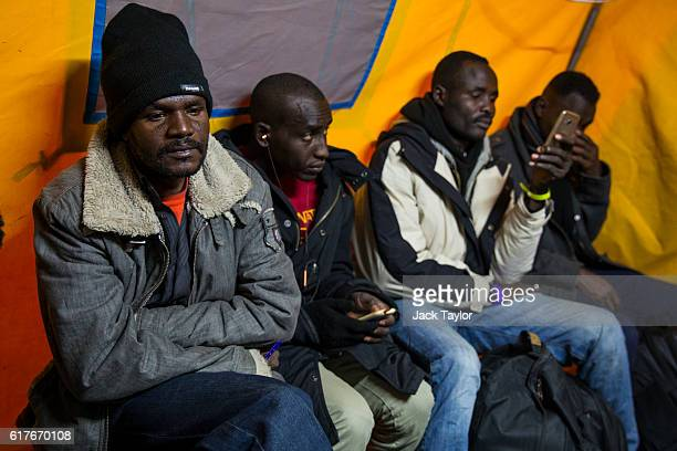 Migrants wait in a tent at a reception point outside the Jungle migrant camp before boarding buses to refugee centres around France on October 24...