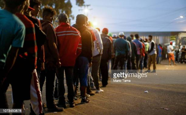 Migrants wait in line to receive dinner outside a temporary shelter set up for members of the 'migrant caravan' on November 27 2018 in Tijuana Mexico...