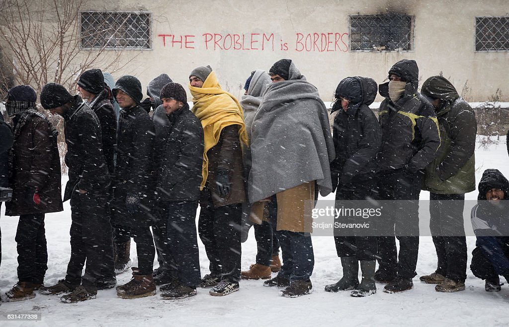 Migrants wait in line to receive free food as snow falls outside a derelict customs warehouse on January 11, 2017 in Belgrade, Serbia. It is estimated that around 1, 000 migrants are sleeping rough in Serbia, enduring temperatures as low as 20 degrees celcius.