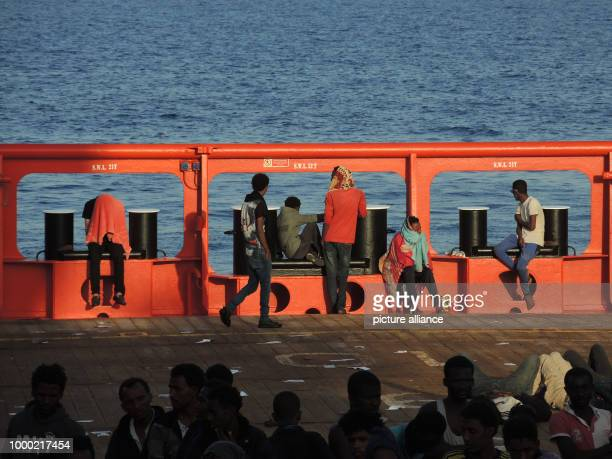 Migrants wait in the cargo section of a civilian ship for their transfer onto the rescue ship 'Aquarius' in the Mediterranean 27 June 2017 The aid...