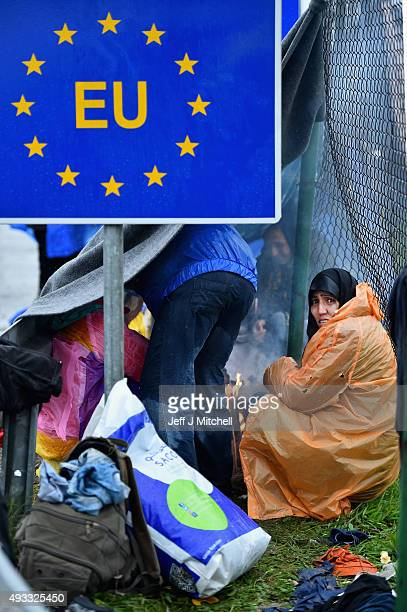 Migrants wait in the rain at the Trnovec border crossing with Slovenia as restrictions on movements have produced bottlenecks on Croatia's borders,...