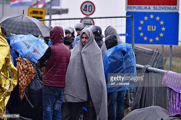 Migrants wait in the rain at the Trnovec border crossing with Slovenia as restrictions on movements have produced bottlenecks on Croatia's borders on...