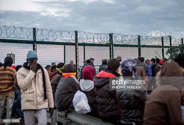 Migrants wait near a Eurotunnel terminal in Coquelles near Calais northern France on July 29 2015 One man died on July 29 in a desperate attempt to...