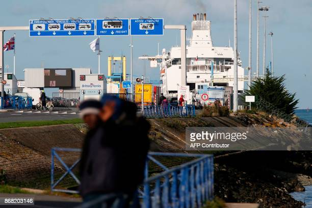 Migrants wait near the port of Ouistreham near Caen northwestern France on October 30 2017 Migration is a hot button issue in Europe and politicians...