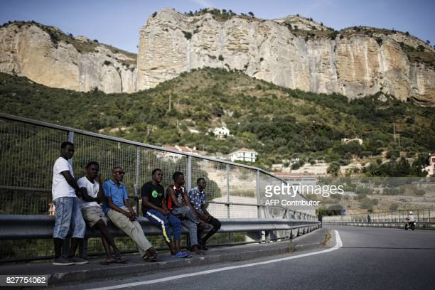 Migrants wait on a road next to the Roya River on August 8 2017 in Ventimiglia close to the French border / AFP PHOTO / Marco BERTORELLO
