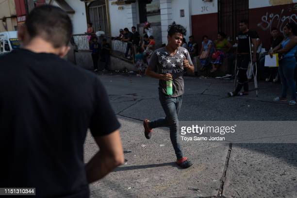 Migrants wait outside the Mexican Commission for Refugee Assistance on June 21 2019 in Tapachula Mexico Hundreds of people queue up outside COMAR...