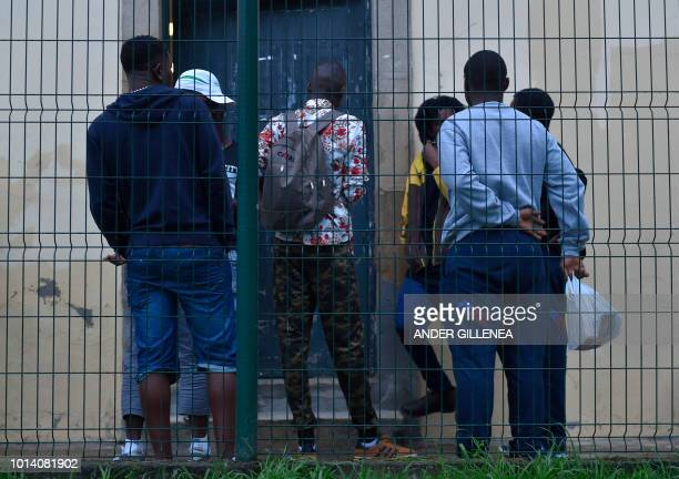Migrants wait outside the migrants reception center in the Spanish Basque city of Irun on August 9 2018 With migrant arrivals to Spain's southern...