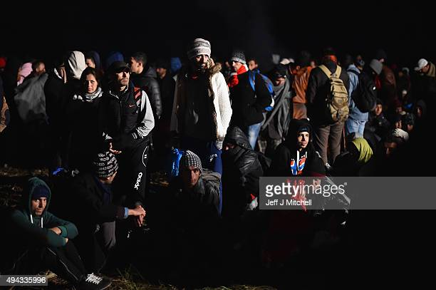 Migrants wait to be escorted by police through fields towards a holding camp in the village of Dobova on October 26 2015 in Rigonce Slovenia...