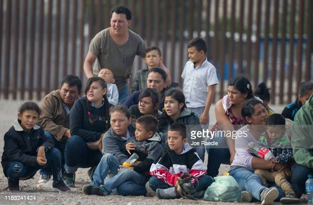 Migrants wait to be processed and loaded onto a bus by Border Patrol agents after being detained when they crossed illegally into the United States...