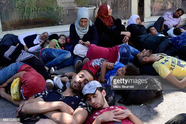 Migrants wait to be registered outside the national stadium on August 12 2015 in Kos Greece Greek police used fire extinguishers and batons to keep...