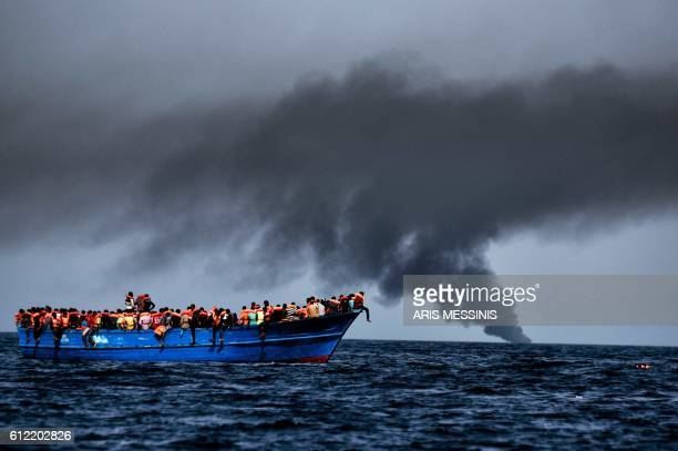 TOPSHOT Migrants wait to be rescued as they drift at sunset in the Mediterranean Sea some 20 nautical miles north off the coast of Libya on October 3...