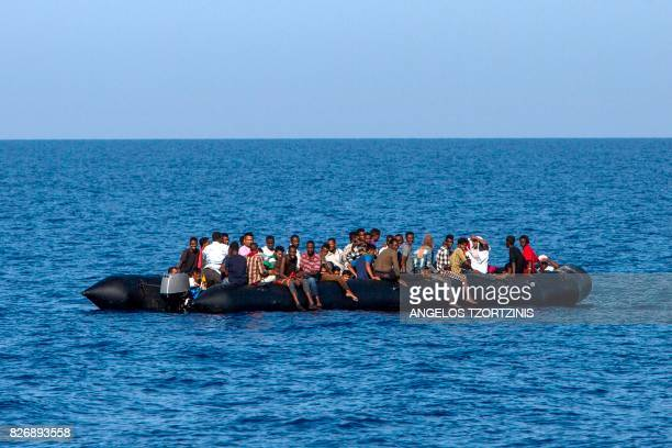 TOPSHOT Migrants wait to be rescued by Italian coast guard in the Mediterranean Sea 30 nautic miles from the Libyan coast on August 6 2017 / AFP...