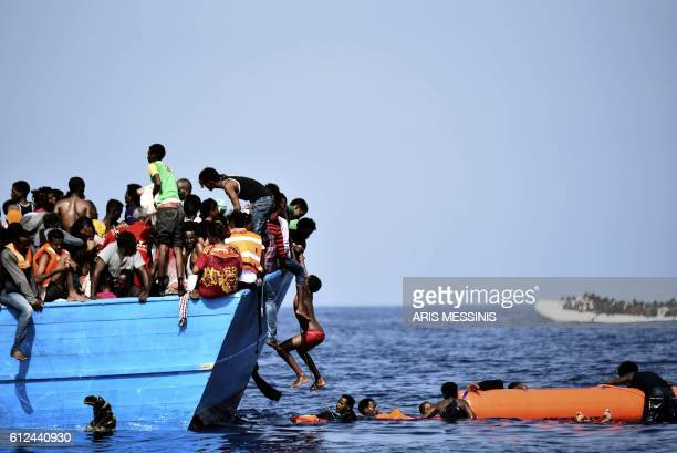 Migrants wait to be rescued by members of Proactiva Open Arms NGO as they drift in the Mediterranean Sea some 12 nautical miles north of Libya on...