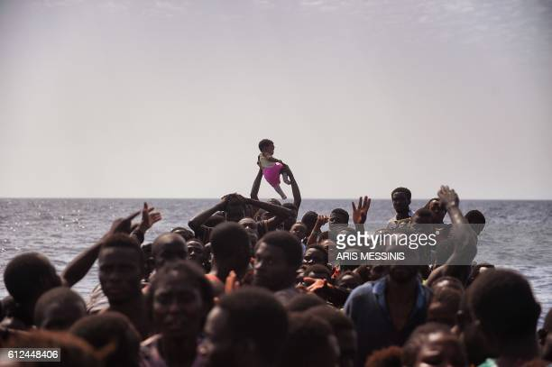 TOPSHOT Migrants wait to be rescued by members of Proactiva Open Arms NGO in the Mediterranean Sea some 12 nautical miles north of Libya on October 4...