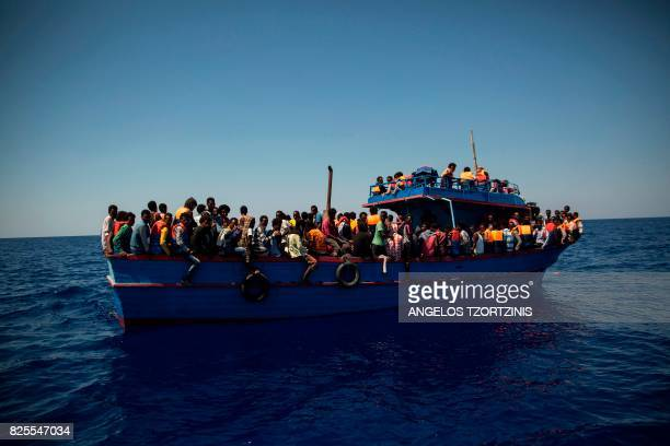 TOPSHOT Migrants wait to be rescued by the Aquarius rescue ship run by nongovernmental organisations SOS Mediterranee and Medecins Sans Frontieres in...