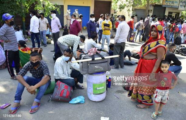 Migrants wait to be thermal screened at Guru Nanak Auditorium before being ferried to the railway station to board Shramik Special trains leaving for...