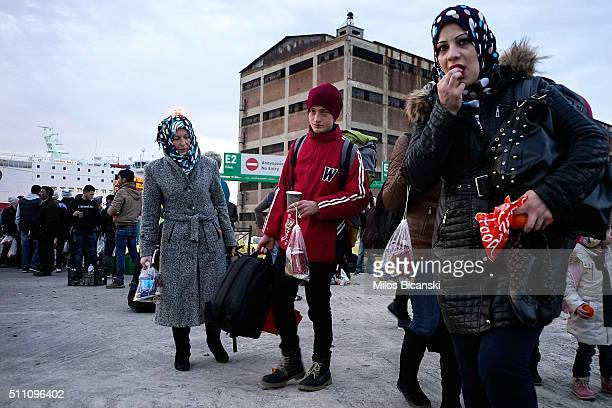 Migrants wait to board a bus after arriving in Pireaus, port of Athens on Februray 18, 2016 in Athens, Greece. Migrants continue to pour into Greece...