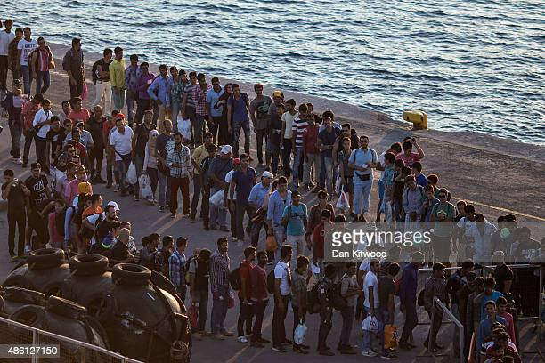 Migrants wait to board a ferry from the island of Kos for transport to the Greek mainland port of Piraeus on August 31 2015 in Kos Greece From...
