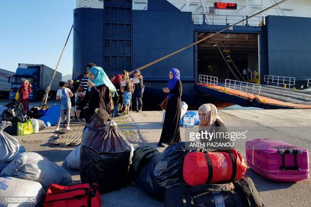 Migrants wait to board a ship at the port of Mytilene to take them to Athens on September 24 2018 Greece has begun transferring hundreds of migrants...