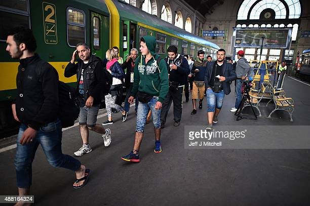 Migrants wait to board a train leaving for the Austrian border at the Keleti railway station on September 14 2015 in Budapest Hungary Migrants who...