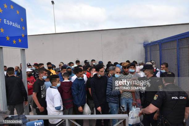 """Migrants wait to cross the border back to Morocco at the Spanish enclave of Ceuta on May 20, 2021. - Spain accused Morocco of """"blackmail"""" on for..."""