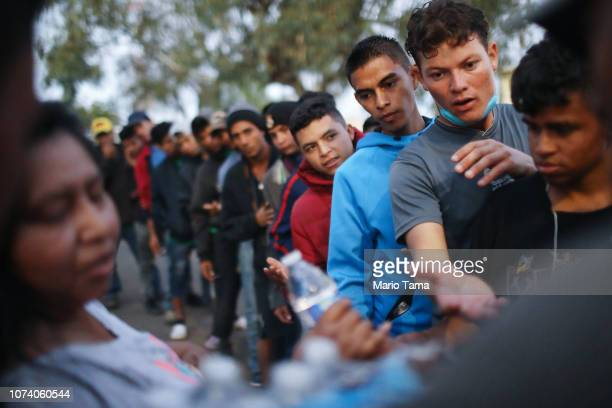 Migrants wait to receive donated food and water outside a temporary shelter set up for members of the 'migrant caravan' on November 28 2018 in...