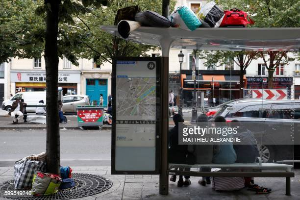TOPSHOT Migrants wait under a bus shelter during the evacuation of a makeshift camp on September 6 2016 in Paris / AFP PHOTO / MATTHIEU ALEXANDRE