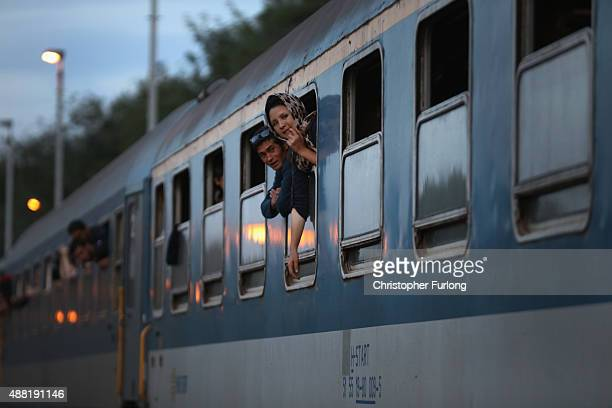 Migrants waive packed on a train at Roszke train station destined for the Austrian border after the hungarian authorities closed the open railway...