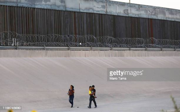 Migrants walk after crossing the border between the U.S. And Mexico at the Rio Grande river, as they walk in El Paso, Texas, on June 27, 2019 as...