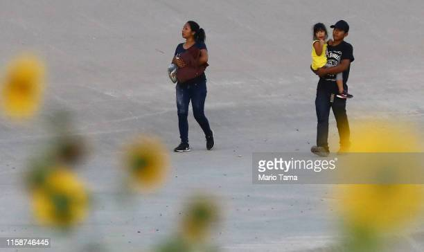 Migrants walk after crossing the border between the US and Mexico at the Rio Grande river as they walk in El Paso Texas on June 27 2019 as taken from...