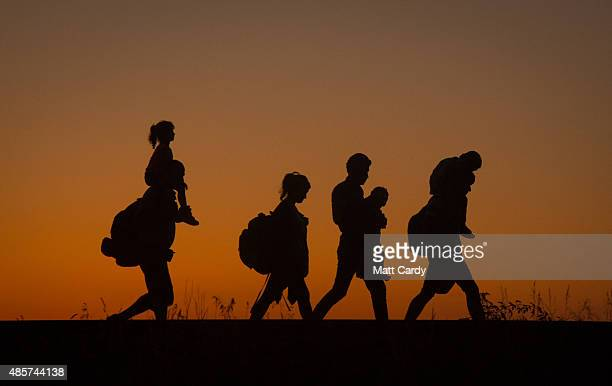 Migrants walk along a railway line after they have crossed the border from Serbia into Hungary close to the village of Roszke on August 29 2015 near...