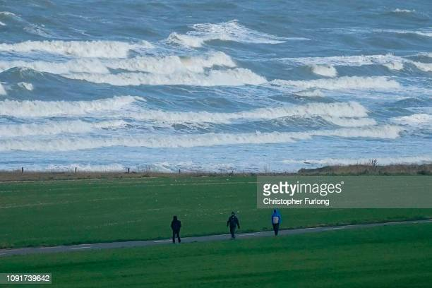 Migrants walk along the coast road at Sangatte on January 09, 2019 in Calais, France. In recent weeks there has been an increase in migrants, many...