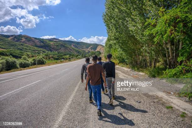 Migrants walk along the hardshoulder of a highway as they make their way from the Iranian border the city of Tatvan, around 200km away, in the...