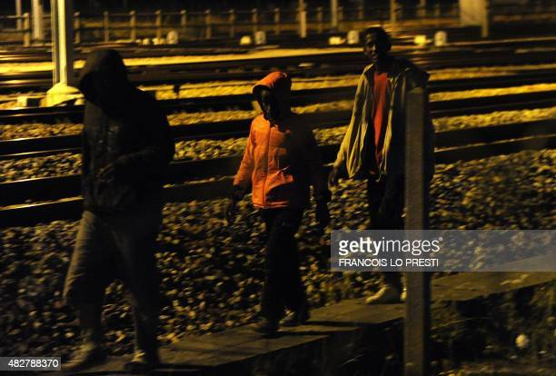 Migrants walk along the railway tracks of the Eurotunnel terminal at the CalaisFrethun station outside the northern French port of Calais on August 2...