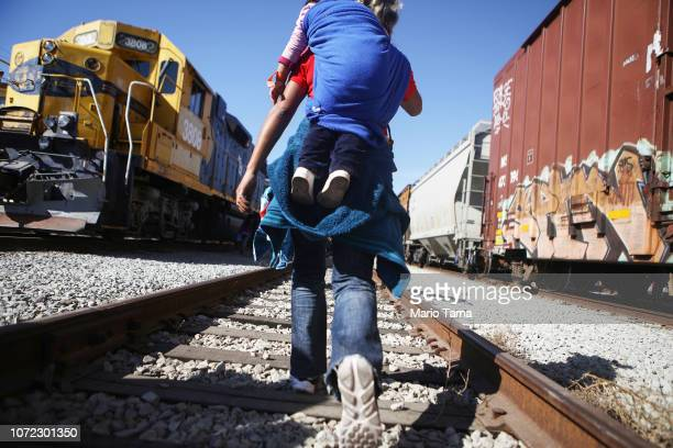 Migrants walk along train tracks toward the USMexico border fence on November 25 2018 in Tijuana Mexico Migrants made their way to the location along...