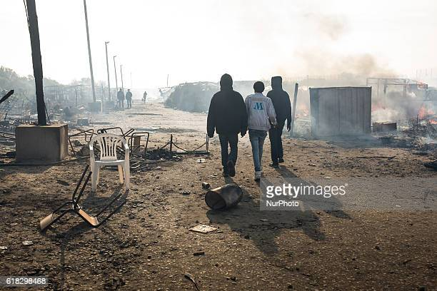 Migrants walk between burned down huts in the Calais Jungle on October 26 2016 Huge fires destroyed a mayor part of the refugee camp today
