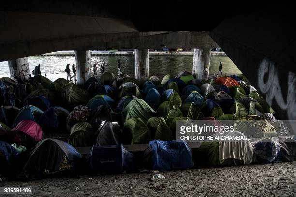 TOPSHOT Migrants walk by tents at a makeshift camp set under a bridge along the canal de SaintDenis in Paris on March 29 2018 / AFP PHOTO /...